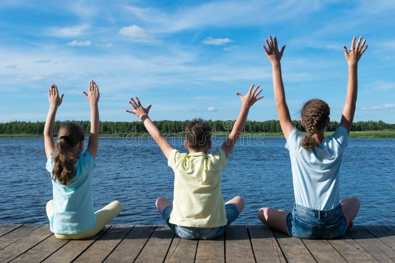 河岸的三个孩子在森林附近做瑜伽 库存图片