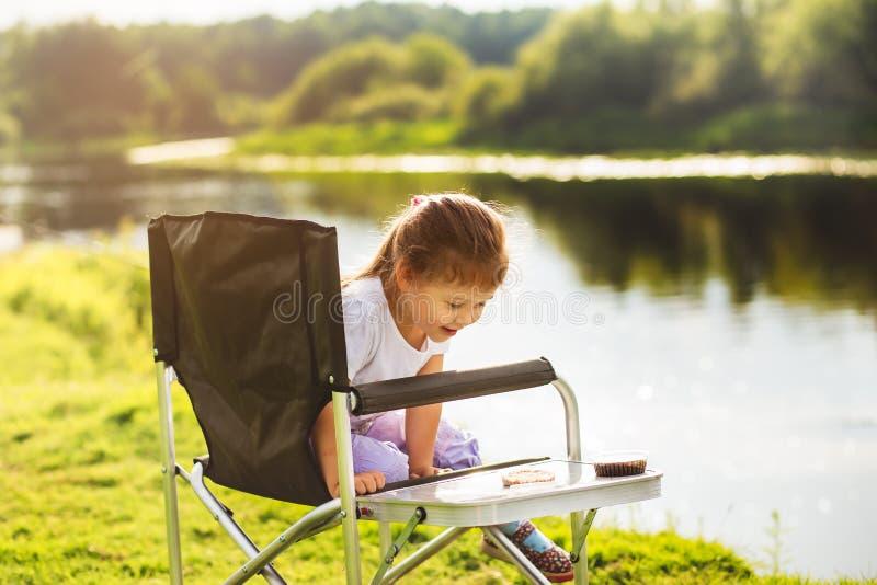 河岸的小女孩一次钓鱼的 免版税库存照片