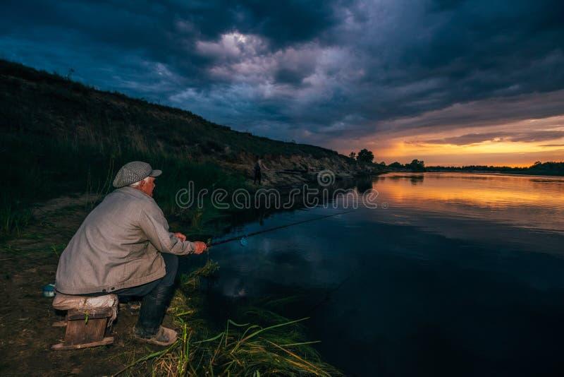河岸的祖父渔夫日落的 库存照片