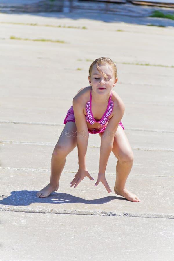 河岸的逗人喜爱的女孩在桃红色泳装 免版税图库摄影