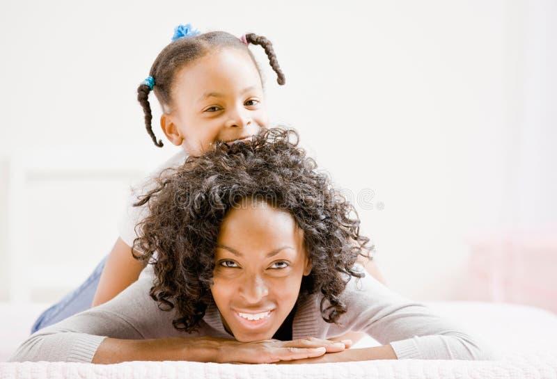 河床女儿放置嬉戏的母亲 免版税库存图片
