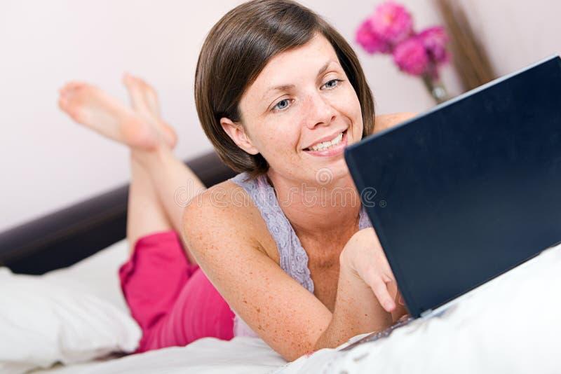 河床女孩相当她的膝上型计算机使用 免版税库存图片