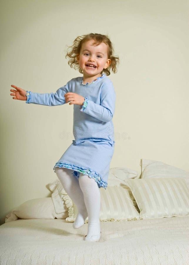 河床女孩跳的年轻人 免版税库存图片
