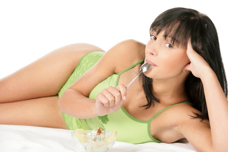 河床奶油色吃的冰位于的妇女 免版税库存图片