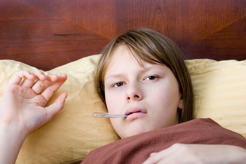 河床评定病态的少年温度的流感女孩 库存照片