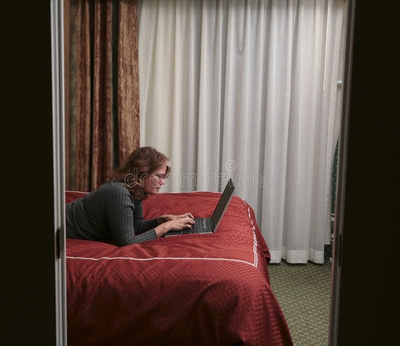 河床读取膝上型计算机的妇女 库存图片