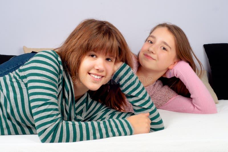河床逗人喜爱的女孩位于的微笑少年 免版税库存照片