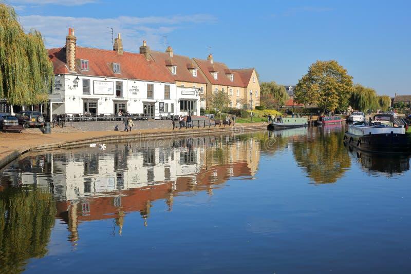 河沿在与被停泊的驳船的秋天在Great Ouse河和传统房子 免版税库存图片