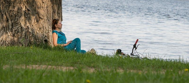 河沿的年轻骑自行车者 免版税库存图片