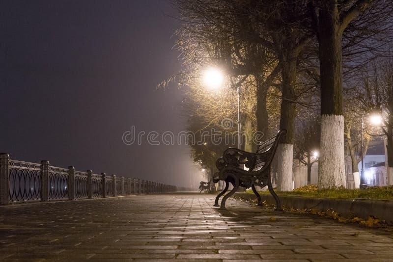 河的城市堤防有灯笼有雾的秋天晚上之前点燃的长凳的 图库摄影