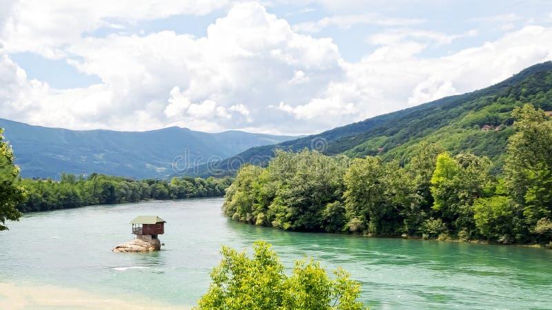 河的德里纳河偏僻的房子在巴伊纳巴什塔 多云天空和山在背景 塞尔维亚 免版税库存照片
