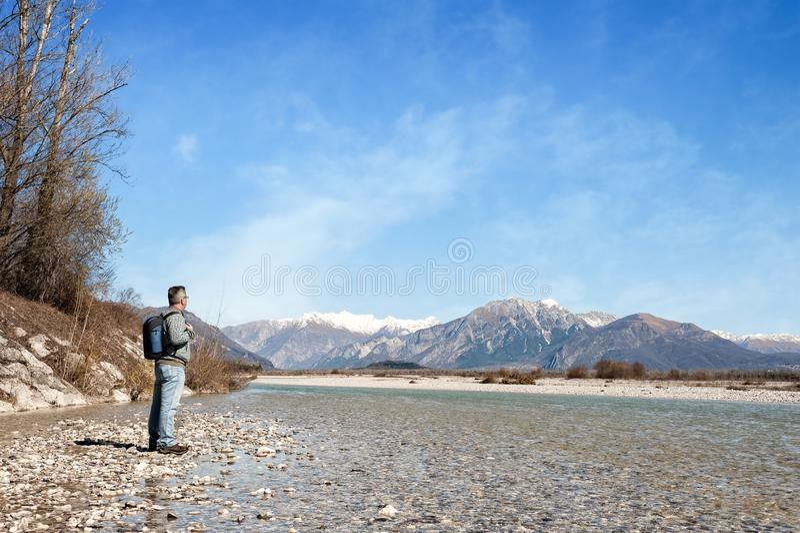 河的河岸的成熟远足者 走往山 库存照片