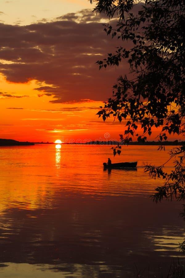 河船的孤立水手在日落 免版税库存图片