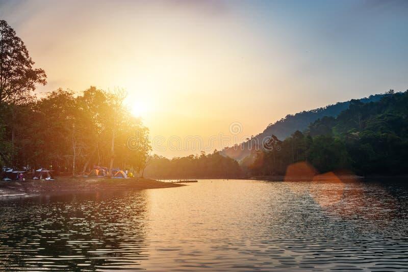 河视图风景在与许多的日出时间在露营地的五颜六色的野营的帐篷 库存图片