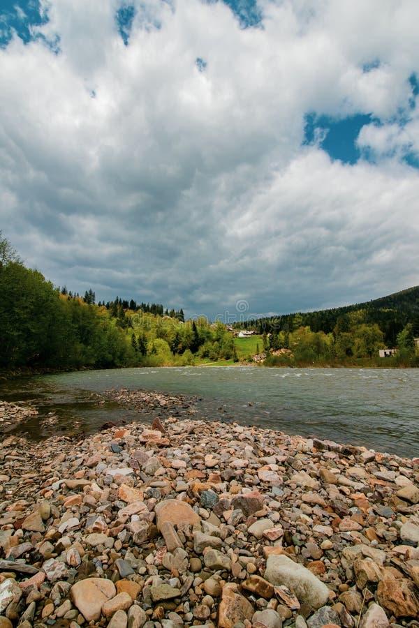 河风景山和天空蔚蓝的在云彩 高山山风景 一个湖的岸有小小卵石的在a 免版税库存照片