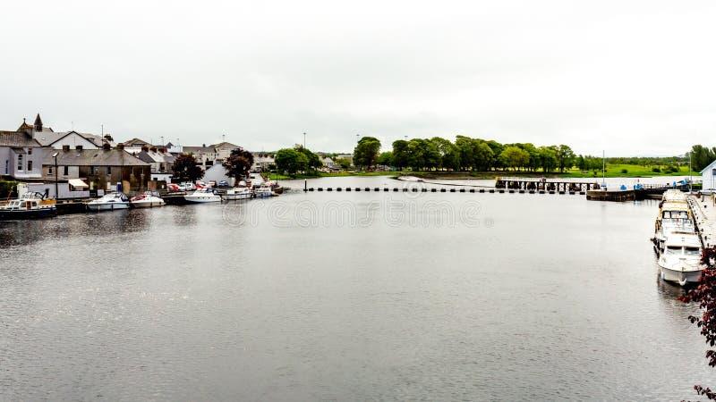 河香农的看法有在与一个公园的岸停住的小船的有在背景中 库存照片