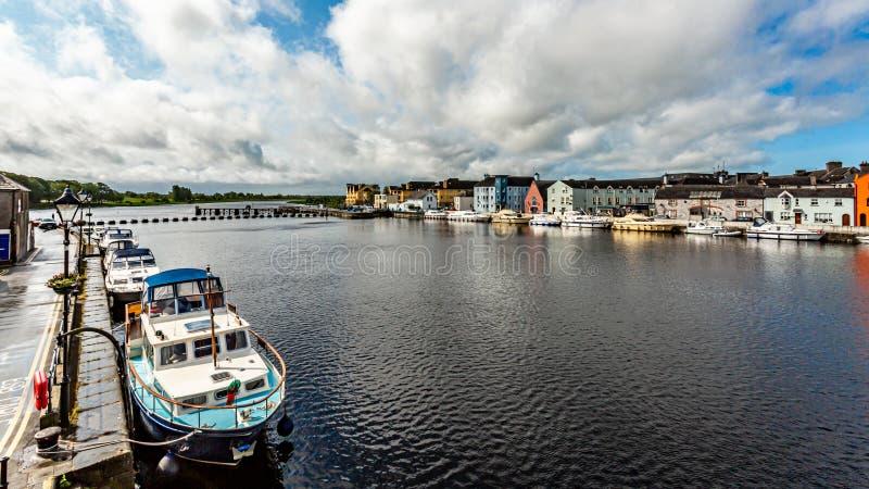 河香农的看法有在海岸和美丽如画的房子停住的小船的在阿斯龙镇  免版税库存照片