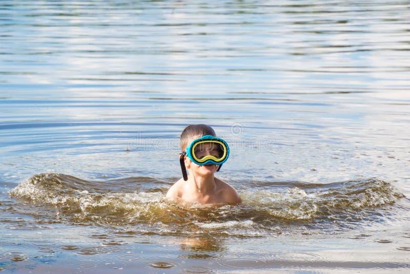 河水的男孩与水肺面具在夏日 免版税库存图片