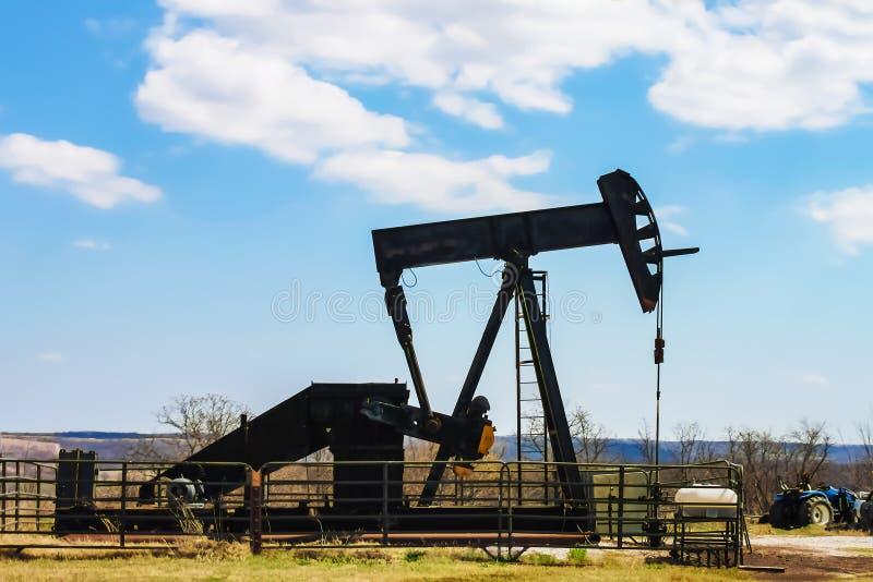 油井泵浦在金属牛篱芭的起重器剪影有在距离和俏丽的天空蔚蓝-拖拉机的蓝色小山的停放对边 免版税库存图片