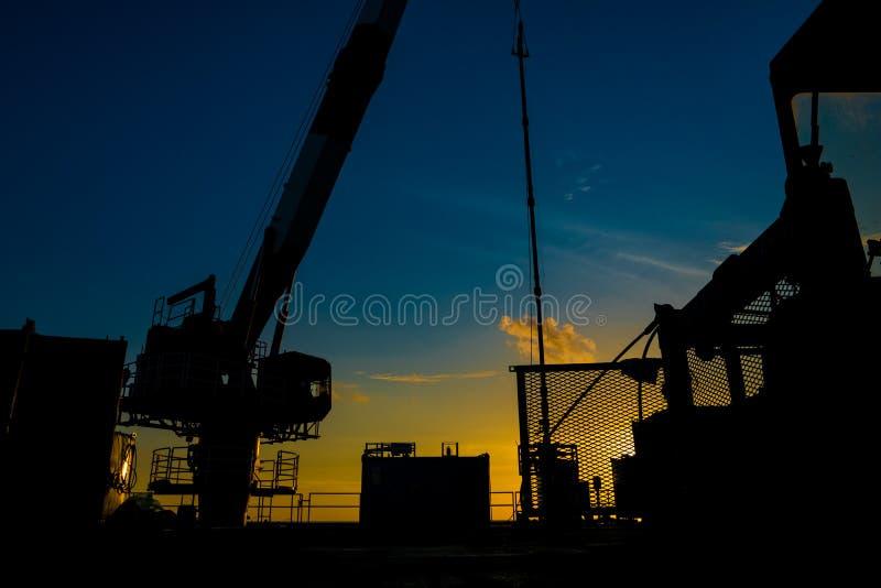 油和煤气泉源平台和好的服务工作者剪影,当工作对穿孔气体和原油水库时 免版税库存图片