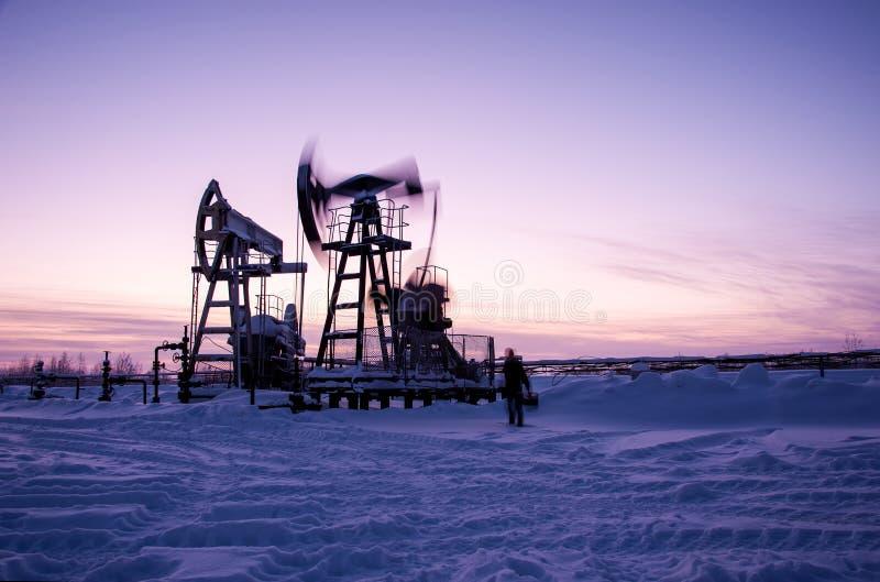 油工作者在油田 抽起重器和工程师冬天日落天空背景的 西西伯利亚 库存图片