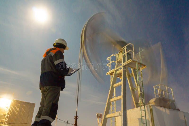 油工作者检查油泵 油钻子、领域泵浦起重器与雪风暴和工作者 常规能源资源概念 免版税库存图片