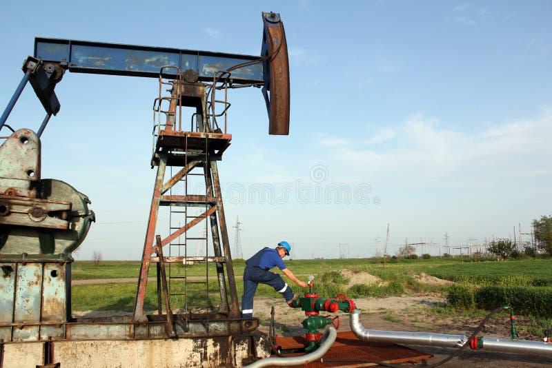油工作者检查泵浦起重器 免版税库存图片