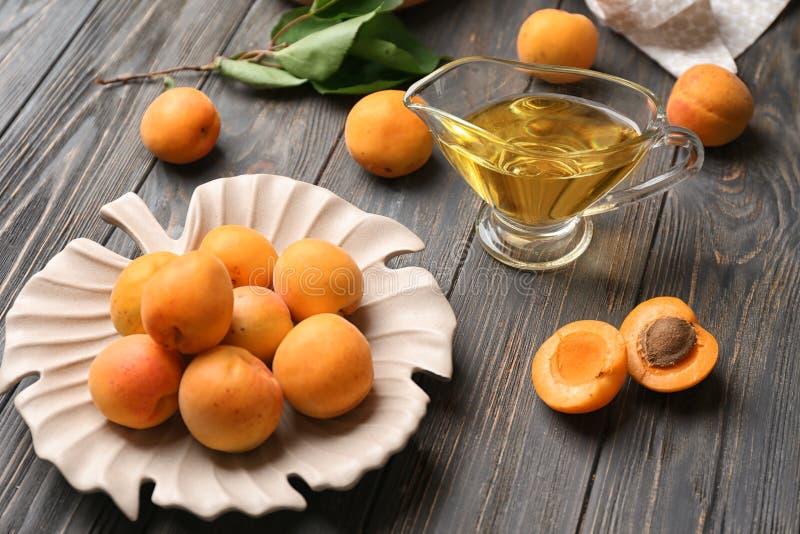 油新鲜的杏子和小汤小船在木桌上的 免版税库存图片