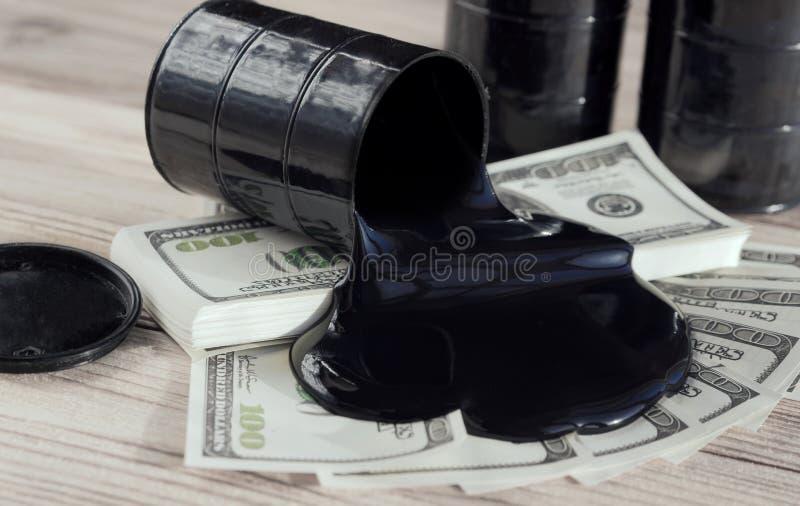 油桶和倾吐的金钱美元货币 交易 替换 石油产业 免版税库存照片