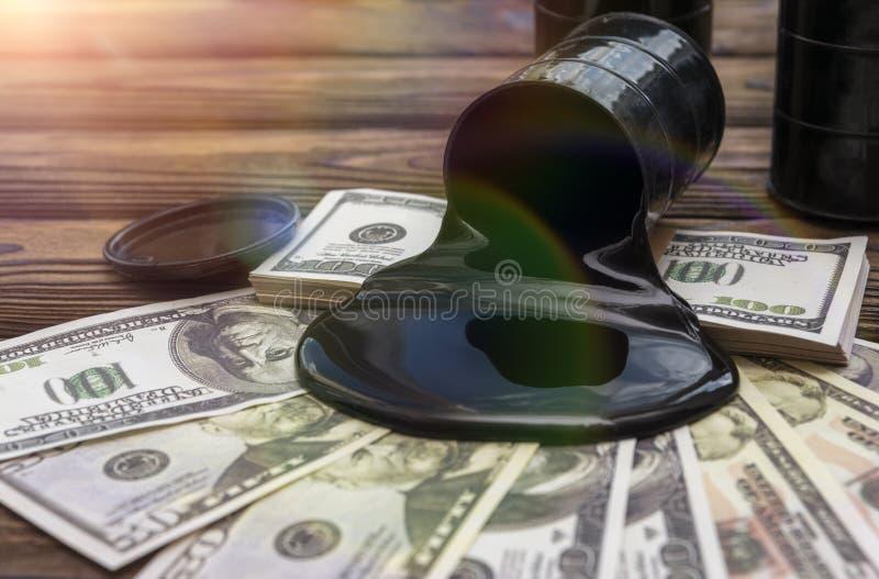 油桶和倾吐的金钱美元货币 库存图片