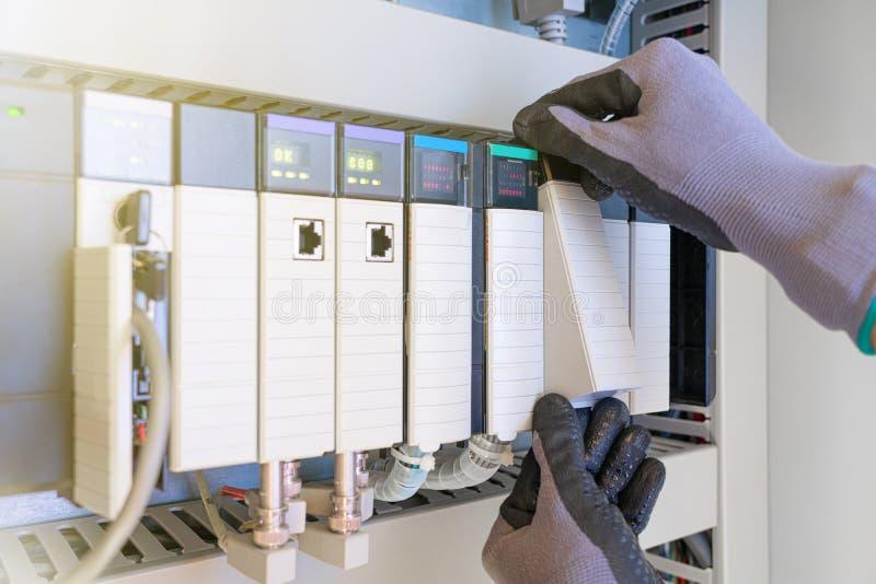 油气过程可编程逻辑控制器PLC输入输出卡的电气仪表技术人员更换 库存照片