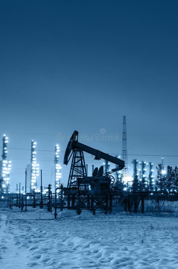 油泵和泉源在精炼厂背景在夜之前 库存图片