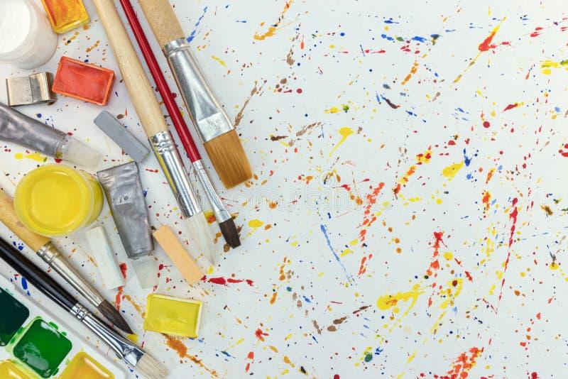 油漆刷、水彩和蜡笔在五颜六色的油漆一滴bac 免版税图库摄影