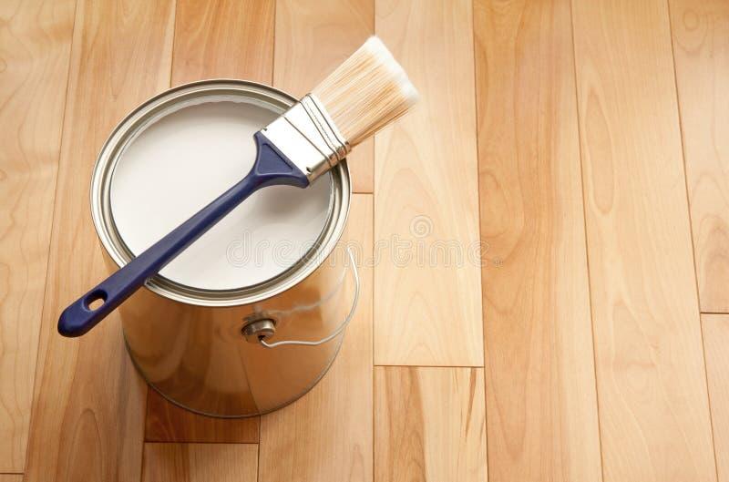 油漆刷和一个罐头在木楼层上的油漆 免版税库存图片