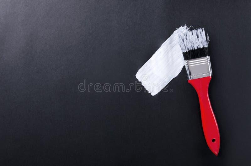 油漆刷,黑表面上的白色冲程顶视图  图库摄影
