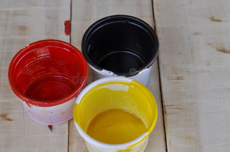 油漆罐头在木桌、红色、黄色和黑色上的色板显示在木桌上 库存图片