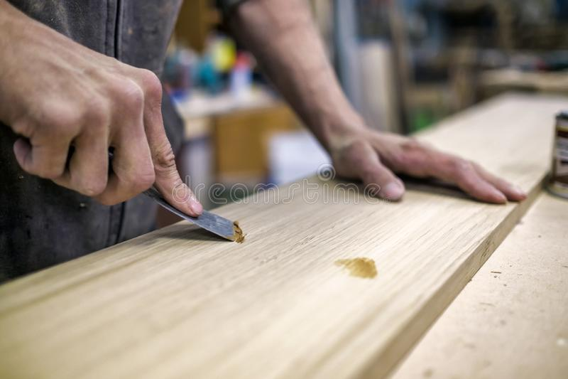 油灰刀在人手上 去除孔从木表面 免版税图库摄影