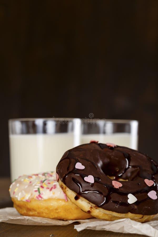 油炸圈饼和一杯在桌上的牛奶 库存图片