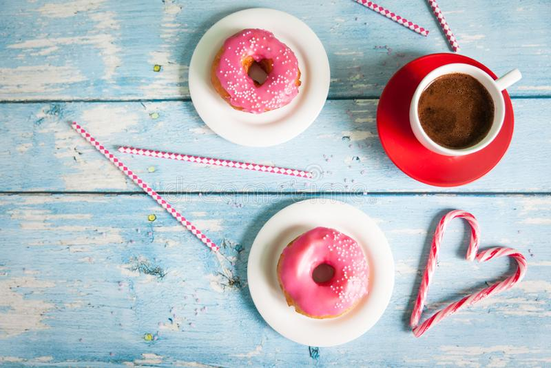 油炸圈饼和咖啡在蓝色木背景 免版税库存图片