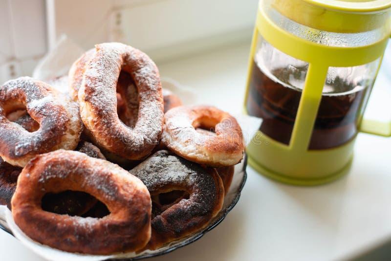 油炸圈饼在糖粉和茶的早餐 免版税库存图片