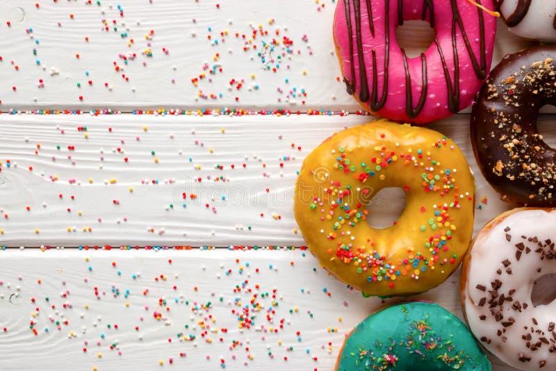 油炸圈饼用在木背景和空间的不同的釉文本的 免版税库存照片
