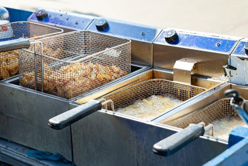 油炸土豆 在炸锅的煮沸的油油煎的薯条 免版税库存照片