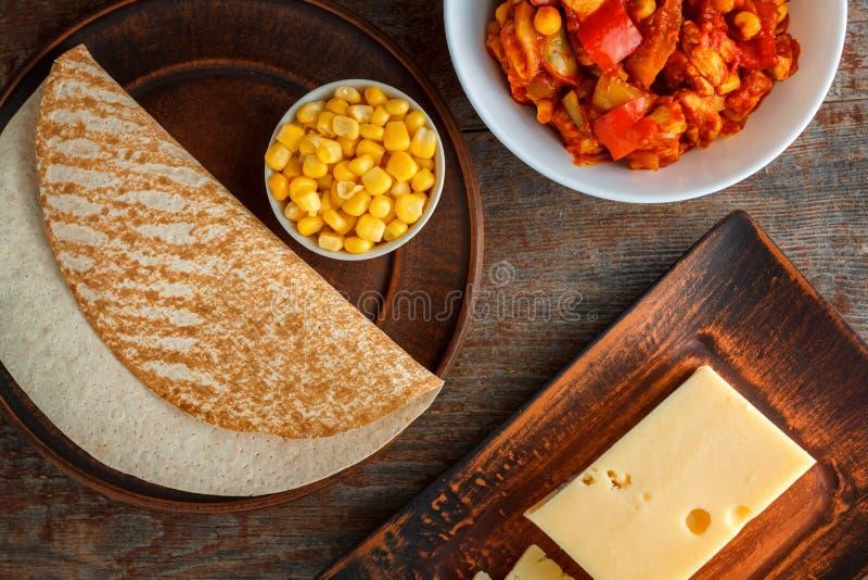 油炸玉米粉饼的, burito,炸玉米饼成份,在一张木桌上 免版税库存图片