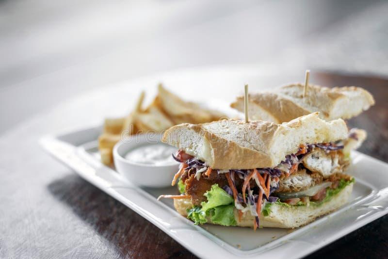 油煎了与凉拌卷心菜沙拉薯条和调味汁的被打击的鲜鱼内圆角三明治 免版税图库摄影