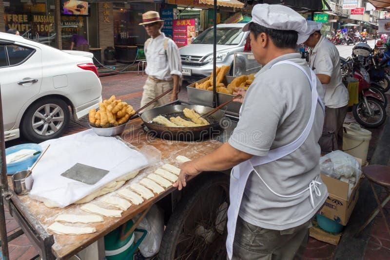 油煎在一个街道食物推车的人churros在唐人街,曼谷,泰国 库存照片