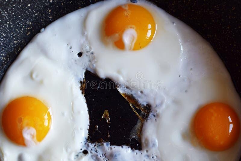 油煎在平底锅的三个鸡蛋顶视图  库存图片