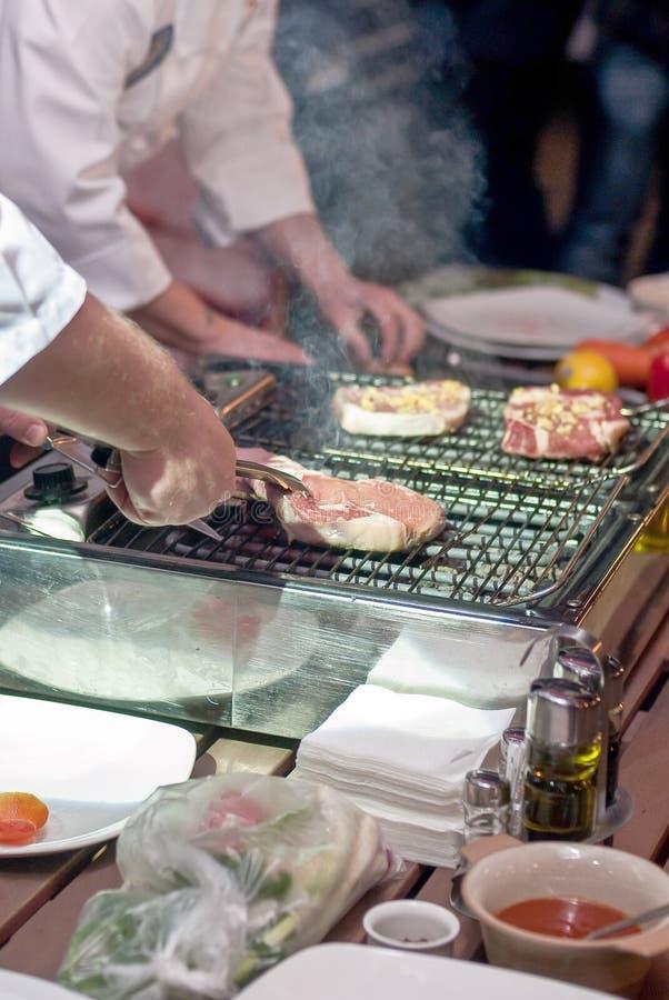 油煎在格栅的制服的厨师人肉牛排切片 免版税图库摄影