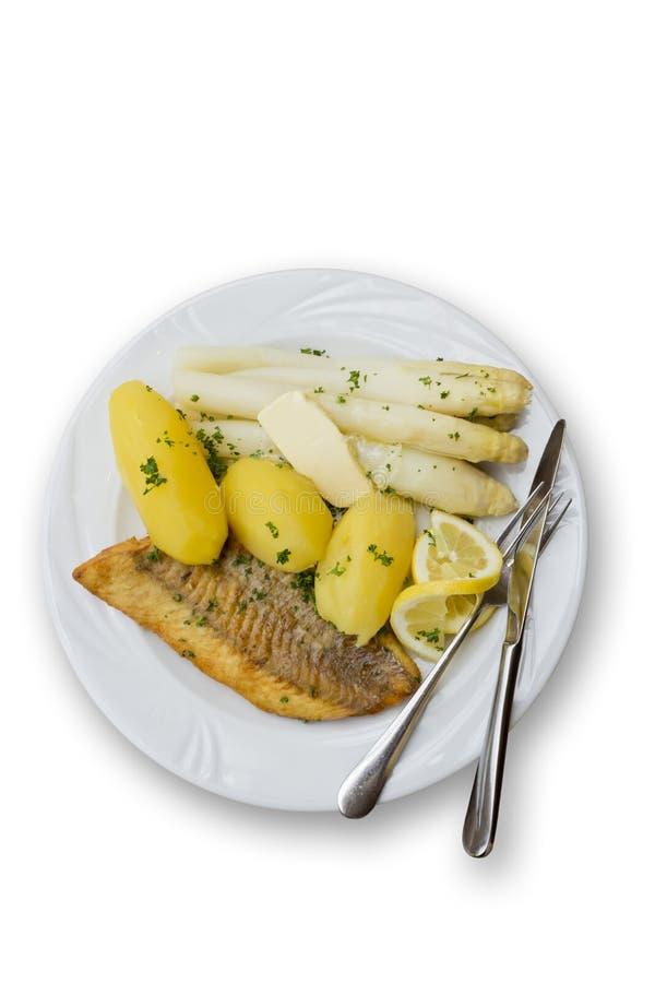 油煎的三文鱼用芦笋、黄油和煮的土豆在板材 免版税库存照片