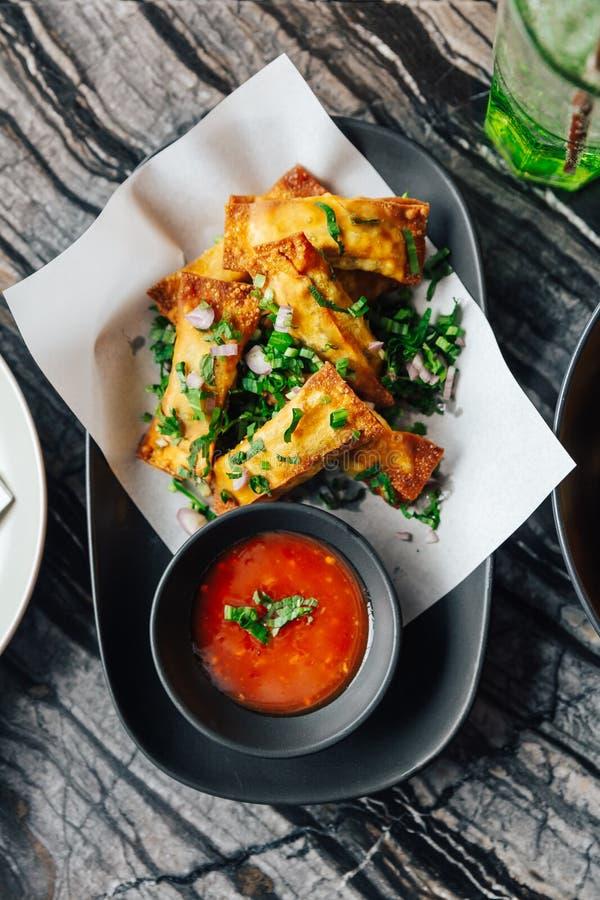 油煎的乳酪馄饨顶视图洒与服务与辣酱的薤和青葱 免版税库存照片