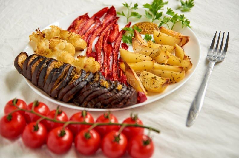 油煎的土豆、茄子、甜椒和花椰菜在用银色叉子和西红柿装饰的白色板材 免版税库存照片